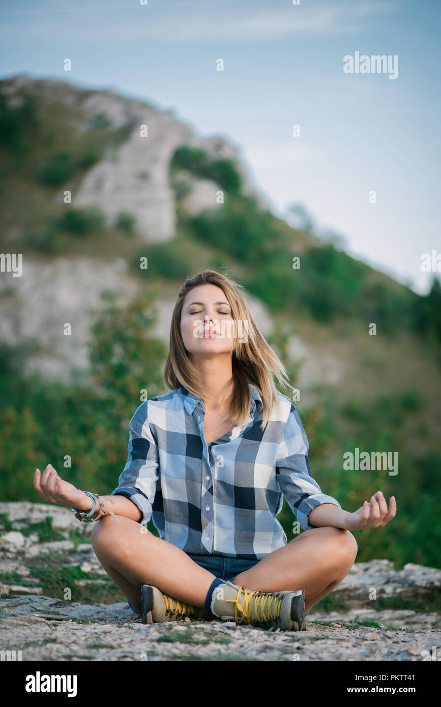 Young beautiful woman doing yoga in nature Stock Photo