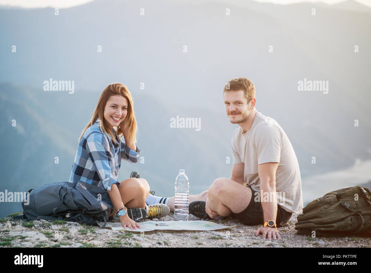 Hiking couple with map - Stock Image