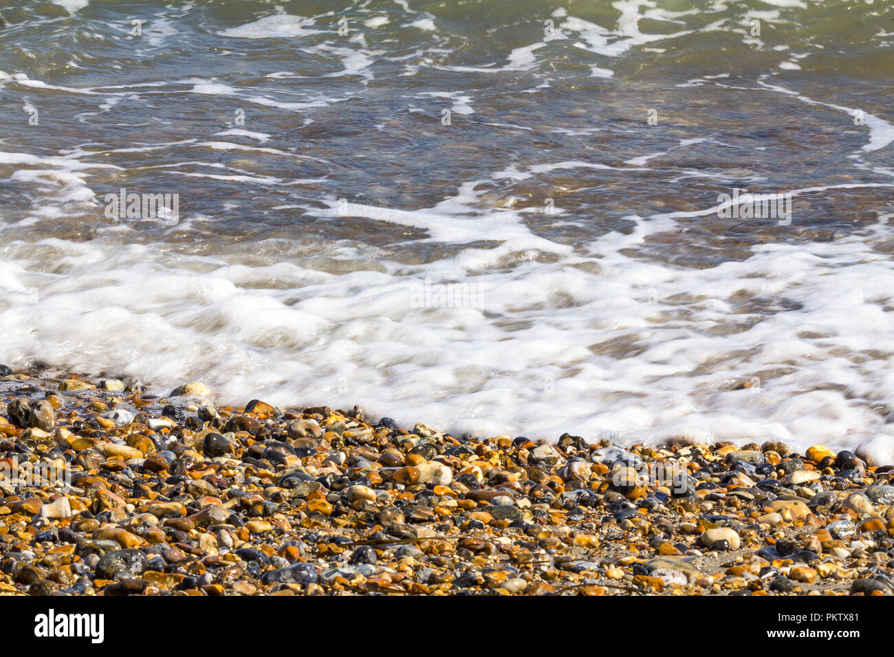 On the beach at Pagham harbour tide comming in. Surf small waves pebbles and shells in late summer. Simple calming waters edge image UK south coast. - Stock Image