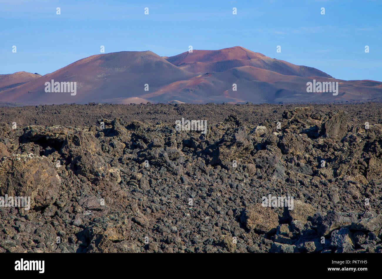 Lava field in front of the Fire Mountains, Montanas del Fuego, Timanfaya National Park at Yaiza, Lanzarote, Canary Islands - Stock Image