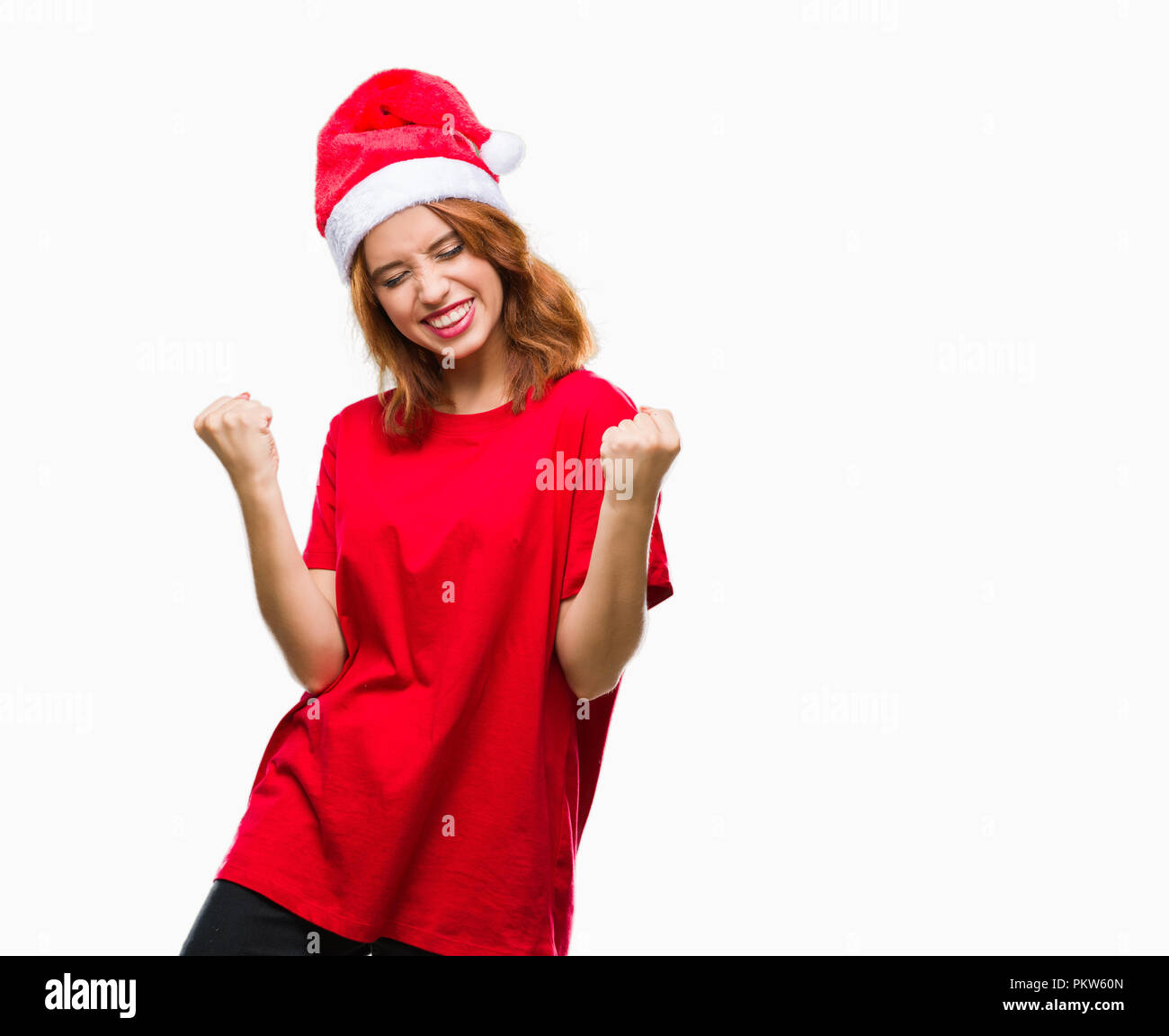 Young beautiful woman over isolated background wearing christmas hat very happy and excited doing winner gesture with arms raised, smiling and screami - Stock Image