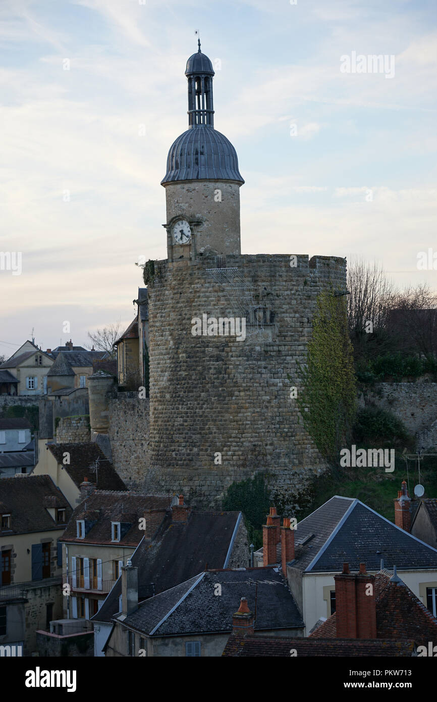 Old stone tower and bell tower in a typical medieval small village with green ivy creeping along - Stock Image