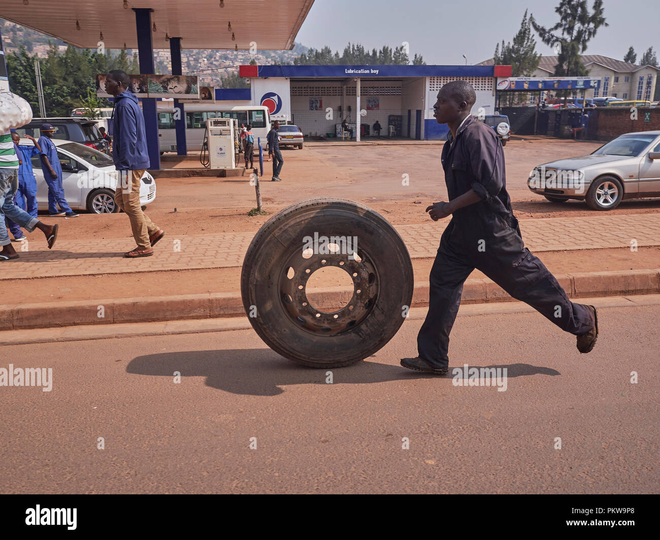 a man in overalls running past a fuel station with a truck tyre/wheel on the road in Kigali, rwanda - Stock Image