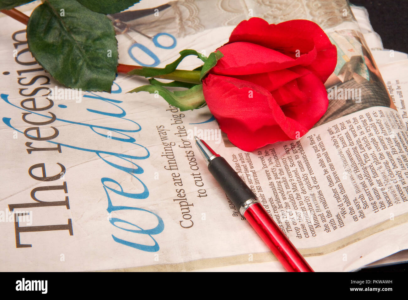 Close-up of newspaper with red rose and pen resting on top of it Stock Photo