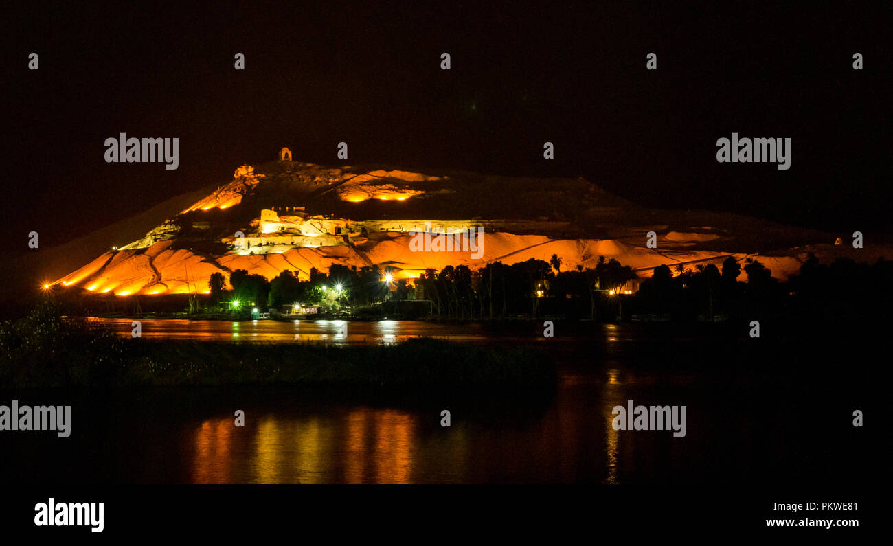 Night view across Nile river with light reflections to hilltop Qubbet el Hawa tomb, Dome of the Winds, and ancient hillside tombs, Aswan, Egypt, Africa - Stock Image