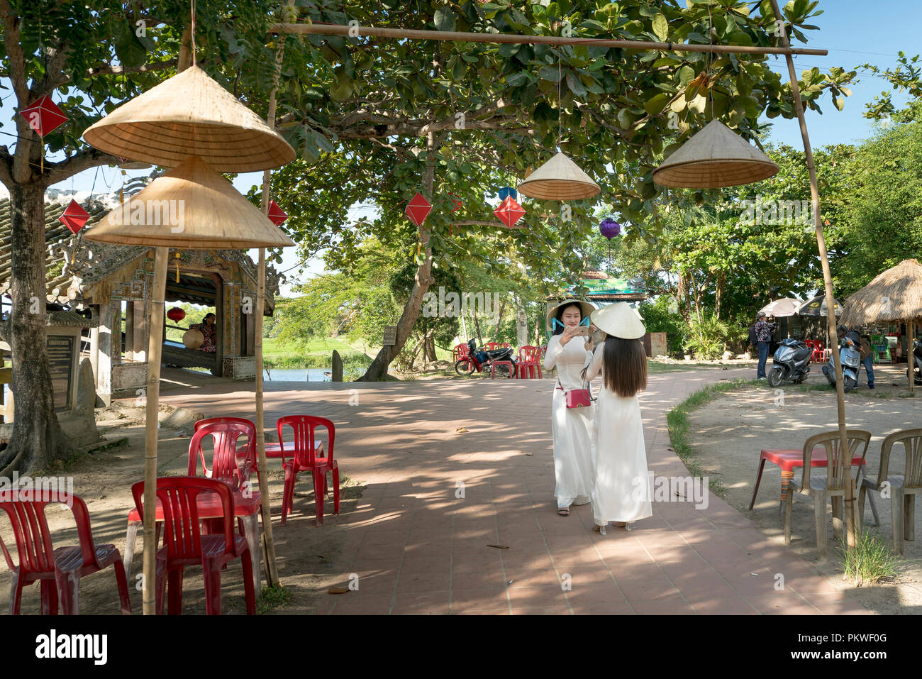 Two Vietnamese girls are gentle in culture traditional white long dress is taking self-portrait for each other at Thanh Thuy Chanh Village in Hue city Stock Photo