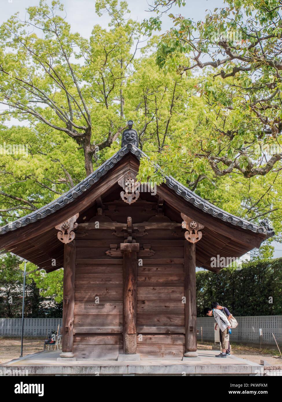 Visitors bowing at temple gate before entering, Motoyamaji, Temple 70 of 88 Temple Shikoku Pilgrimage, Kagawa, Japan - Stock Image
