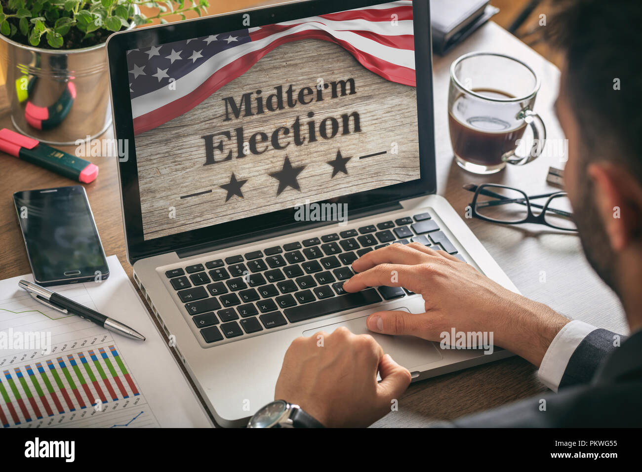 USA electronic vote concept. Businessman with a US of America midterm elections picture onscreen - Stock Image