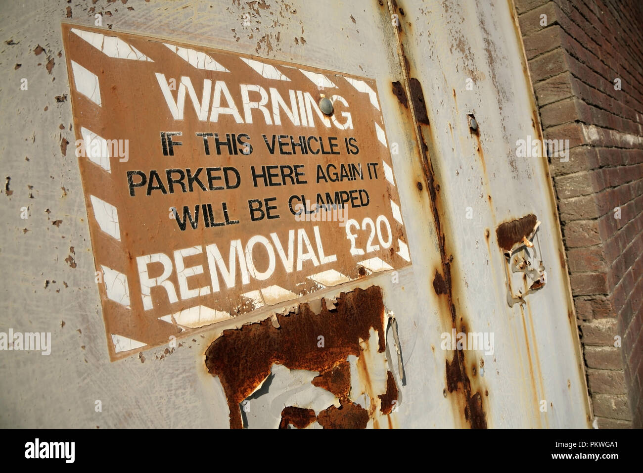 Old sign warning that parked vehicles will be clamped. - Stock Image