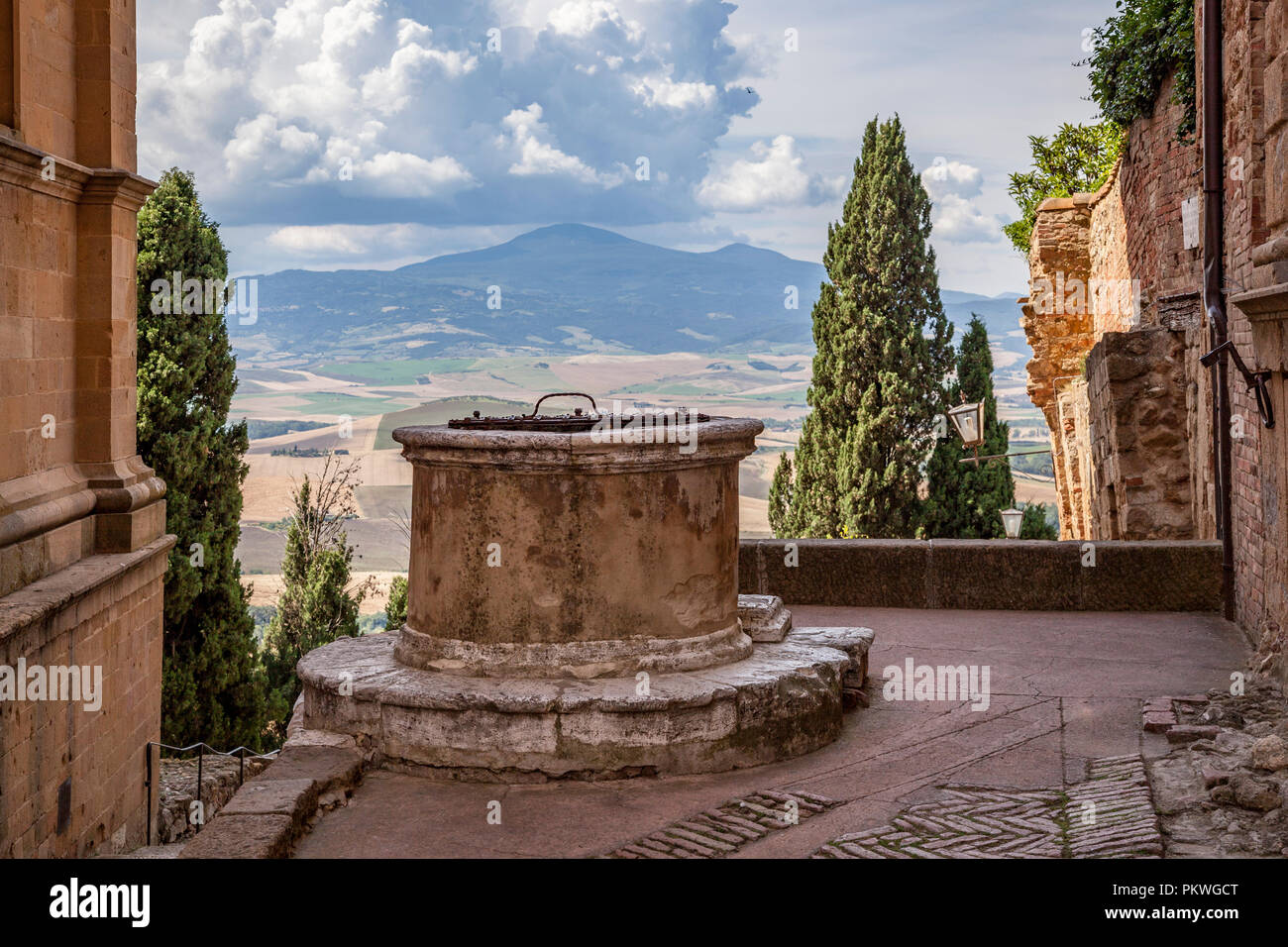 An ancient cistern disused in Pienza (Tuscany - Italy) with Tuscan countryide in the background. Ancienne citerne inutilisée à Pienza (Toscane). - Stock Image