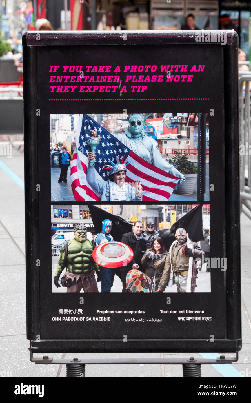 A sign in Times Square warning tourists that the entertainers who dress in costumes expect a tip for posing in photos. - Stock Image
