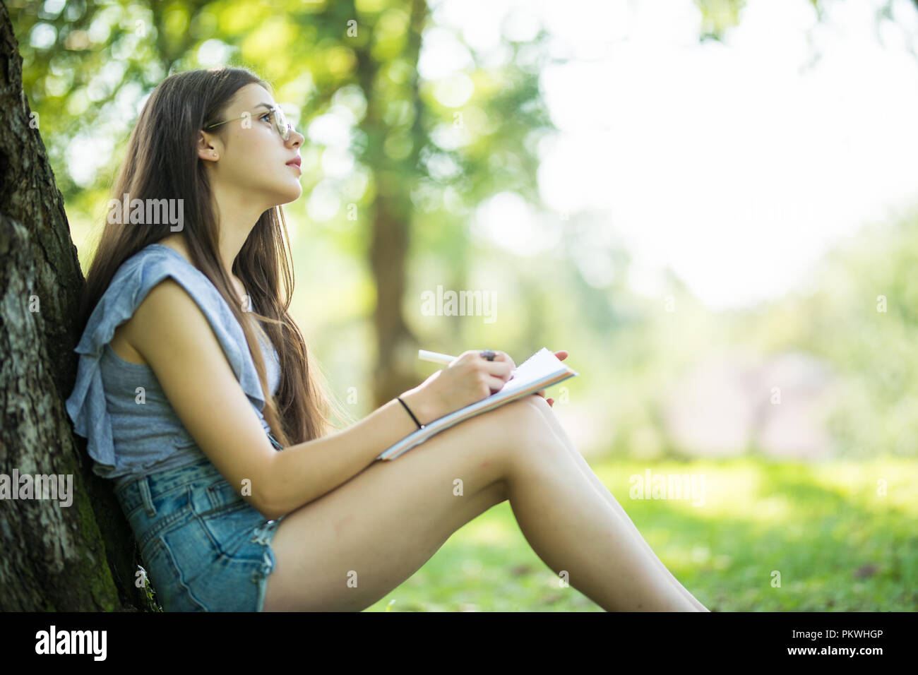 Female student taking notes in her notebook. Young smiling woman sitting in the park doing assignments. - Stock Image