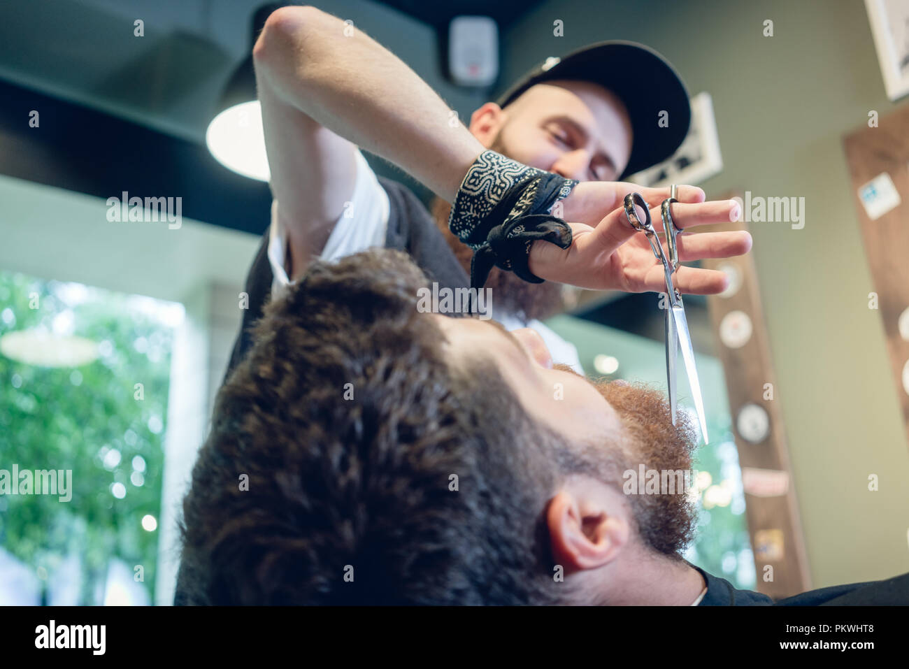 Close-up of the hand of a barber using scissors while trimming - Stock Image