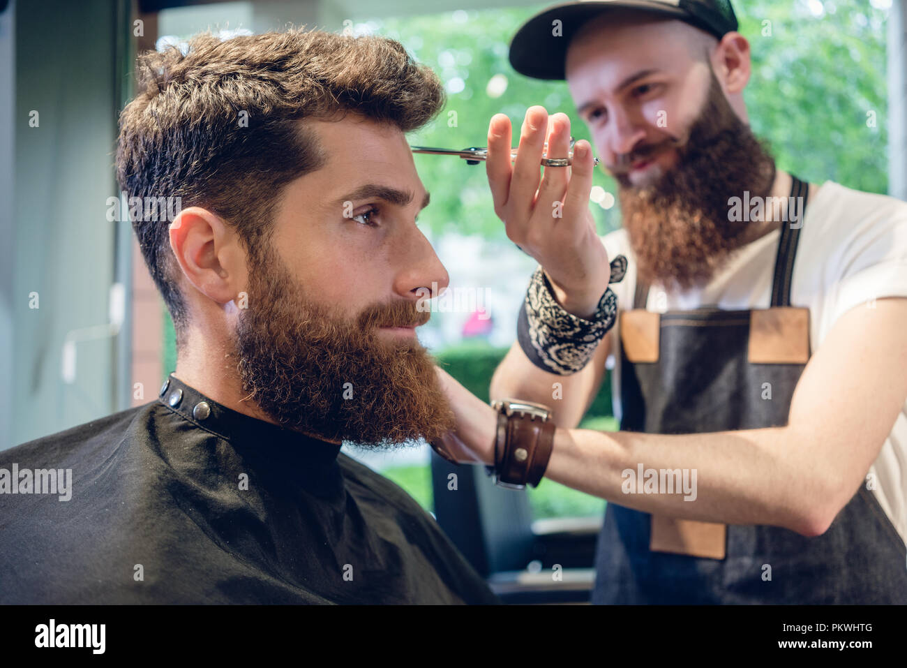 Dedicated hairstylist using scissors and comb - Stock Image