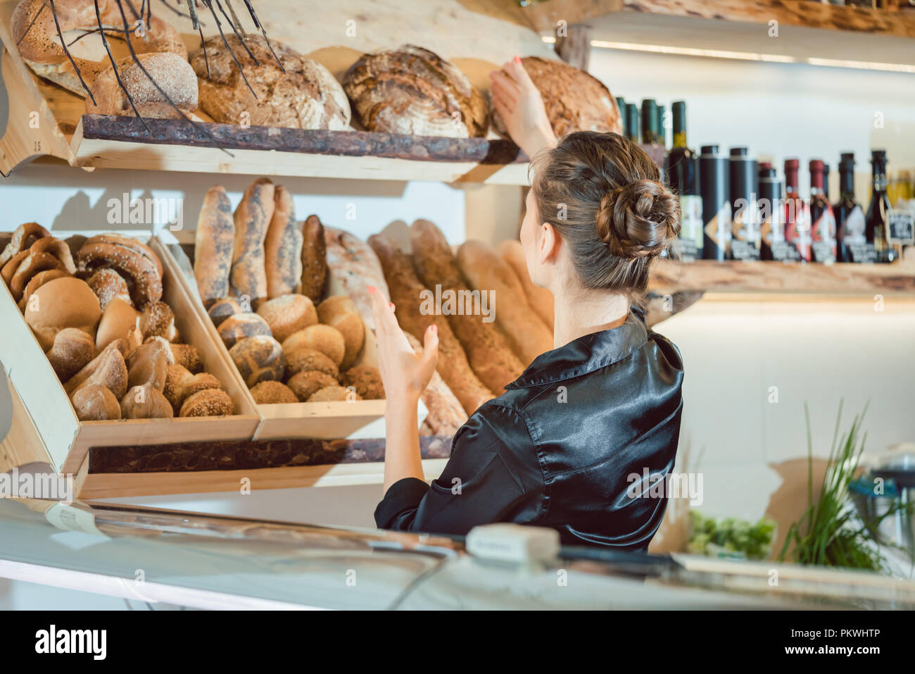 Shop assistant sorting bread to be sold - Stock Image