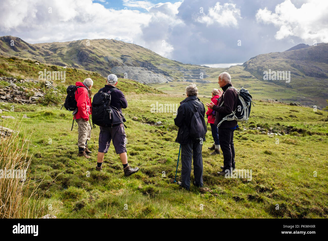 Hikers ramblers in Cwmystradllyn valley looking towards abandoned slate quarry in Snowdonia National Park. Porthmadog, Gwynedd, Wales, UK, Britain Stock Photo