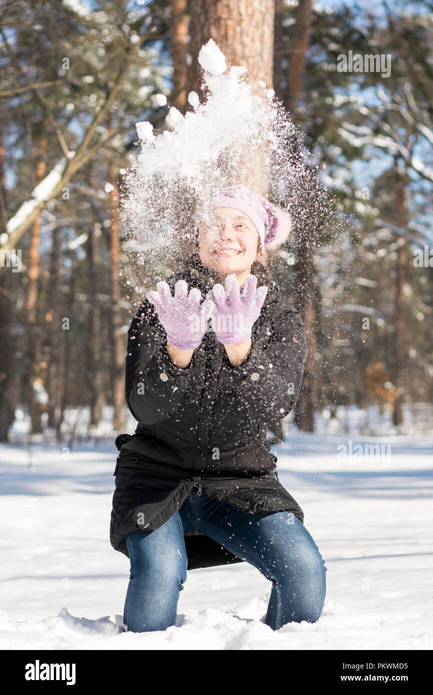Girl throws snow up. Portrait of the beautiful girl throwing snow in the winter. Happy young woman plays with a snow in sunny winter day. vertical pho Stock Photo
