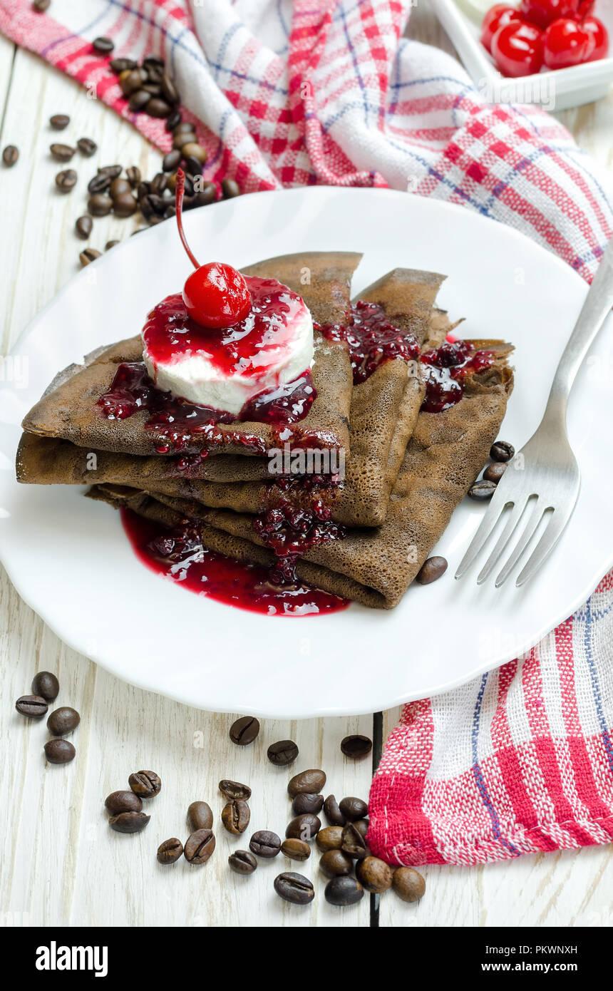 Chocolate pancake with ice cream and raspberry jam. - Stock Image
