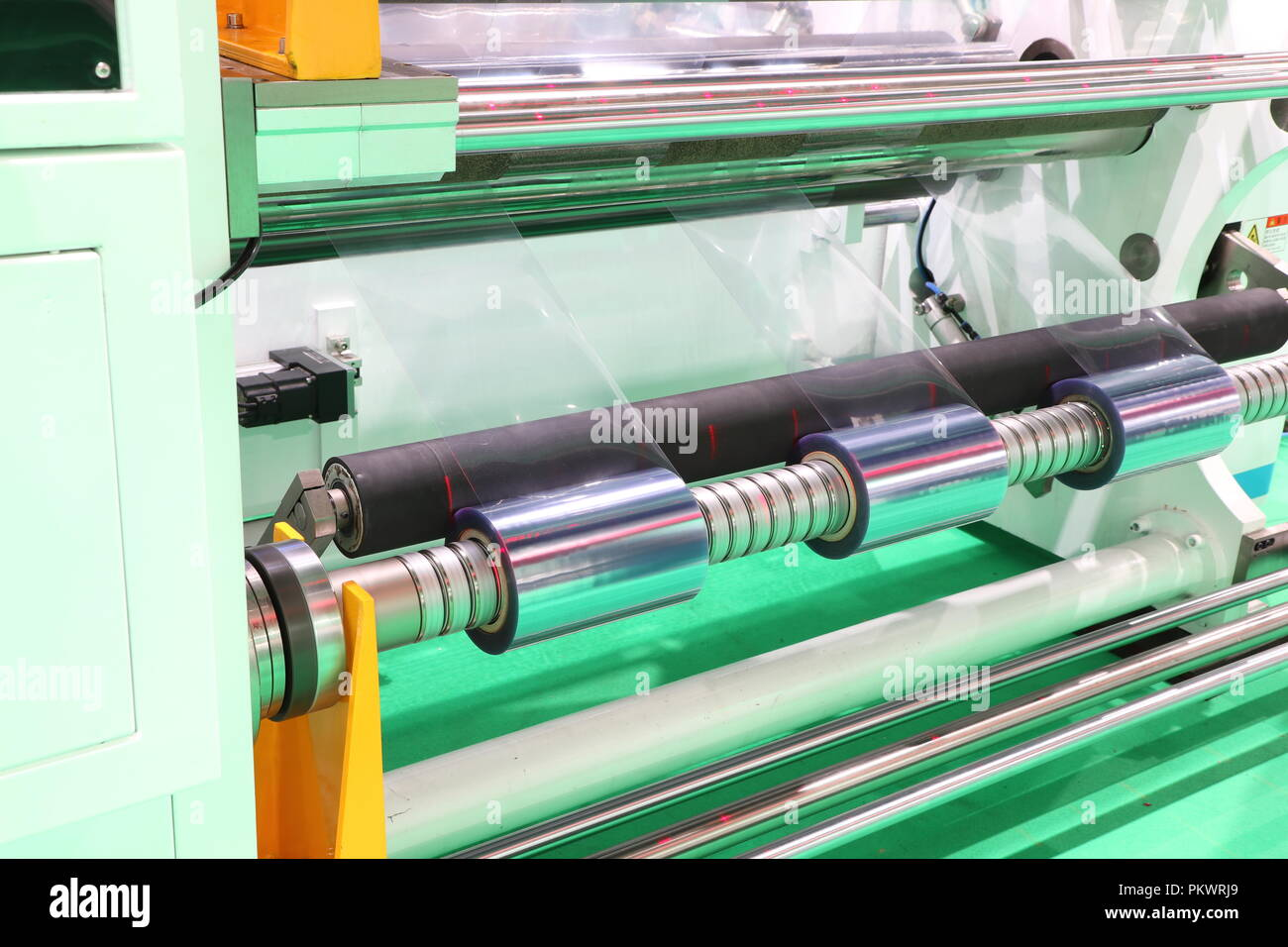 Film Roll slitting machine ; a shearing operation that cuts a large roll of material into narrower rolls Stock Photo