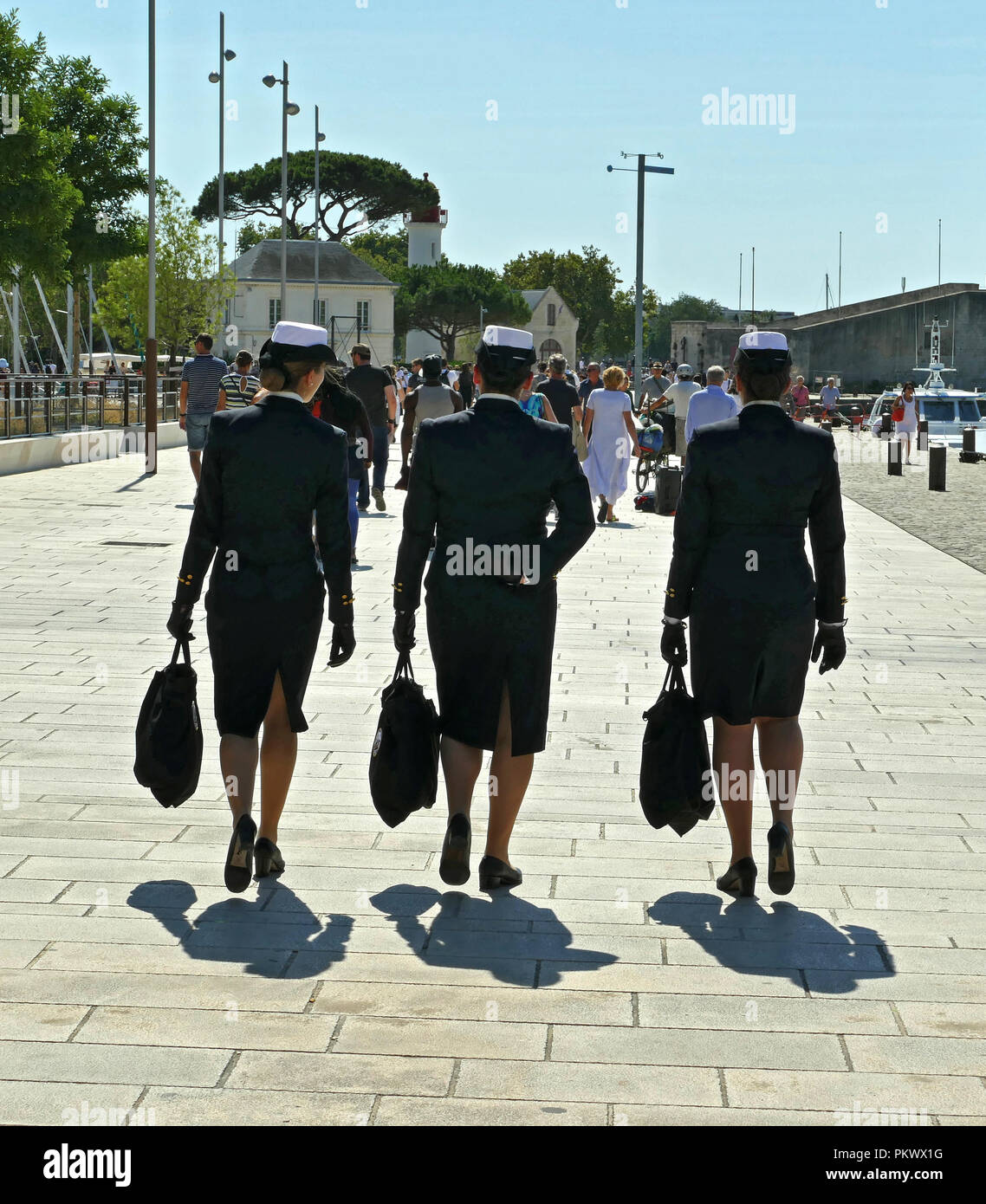 Female crew in uniform walking on a sunny port - Stock Image