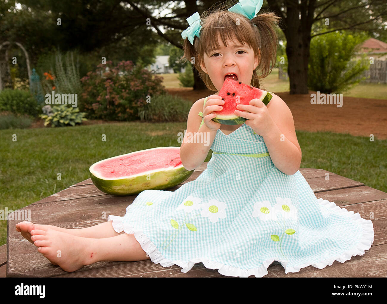Small girl  outdoors with ribbon or hat playing.  Some images old fashion and some she is eating watermelon - Stock Image