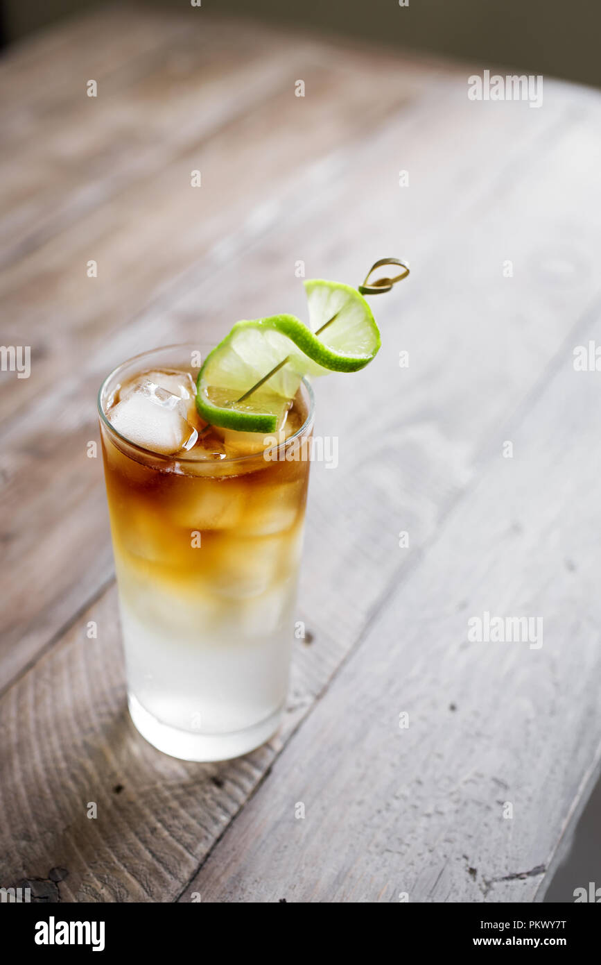 Dark and Stormy Rum Cocktail with Ginger Beer and Lime garnish. Glass of Dark and Stormy Cocktail drink on wooden table, copy space. - Stock Image