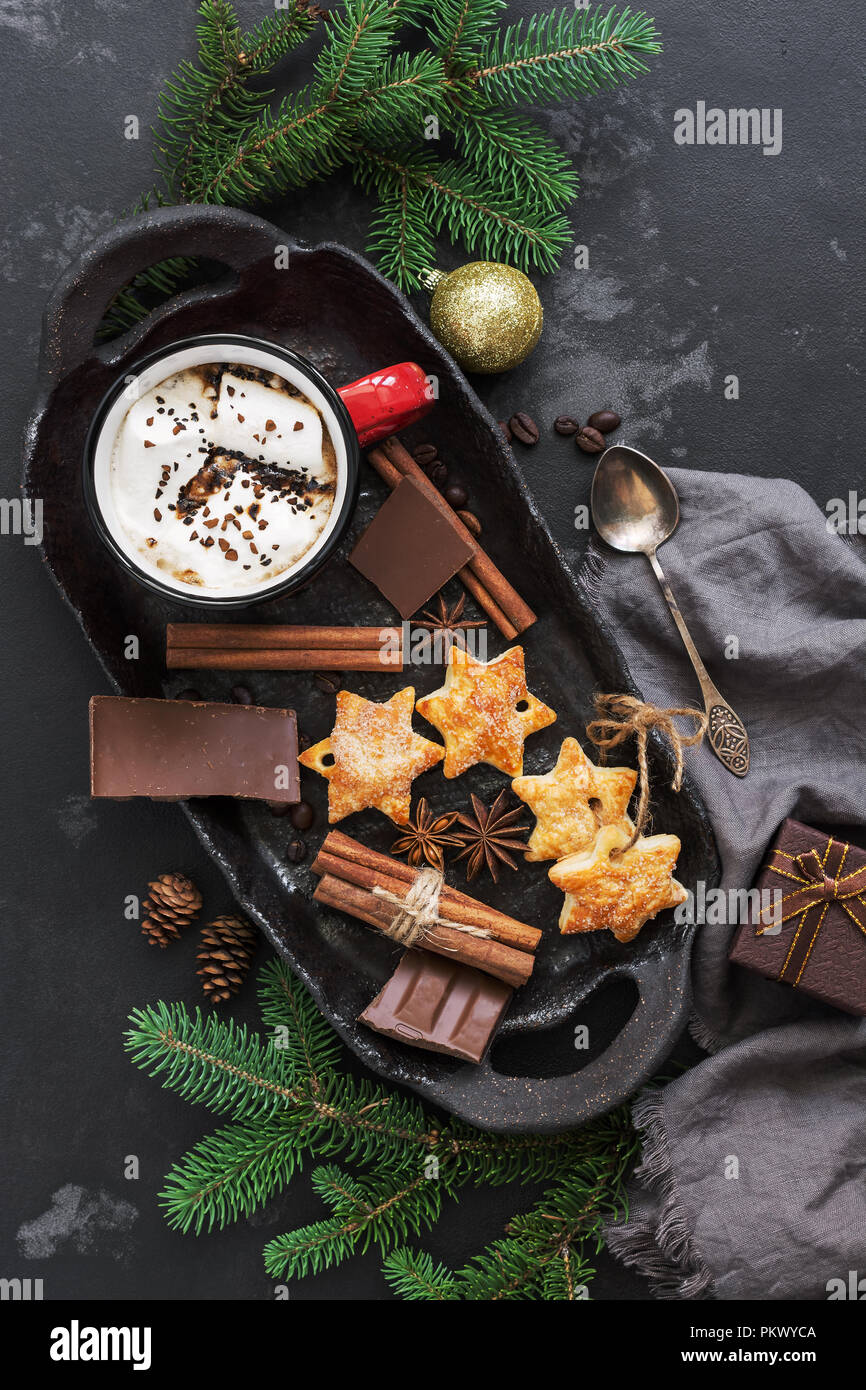 Christmas background with hot chocolate in a red mug with marshmallows, biscuits, spices and chocolate on a dark background. Top view,flat lay - Stock Image