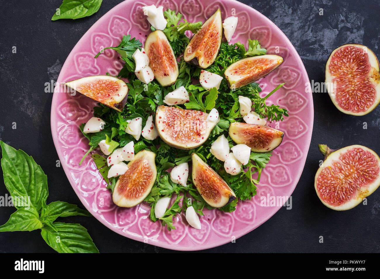 Salad with figs, cheese and greens on a dark concrete background. Dietary healthy food. The view from above, flat lay. Stock Photo