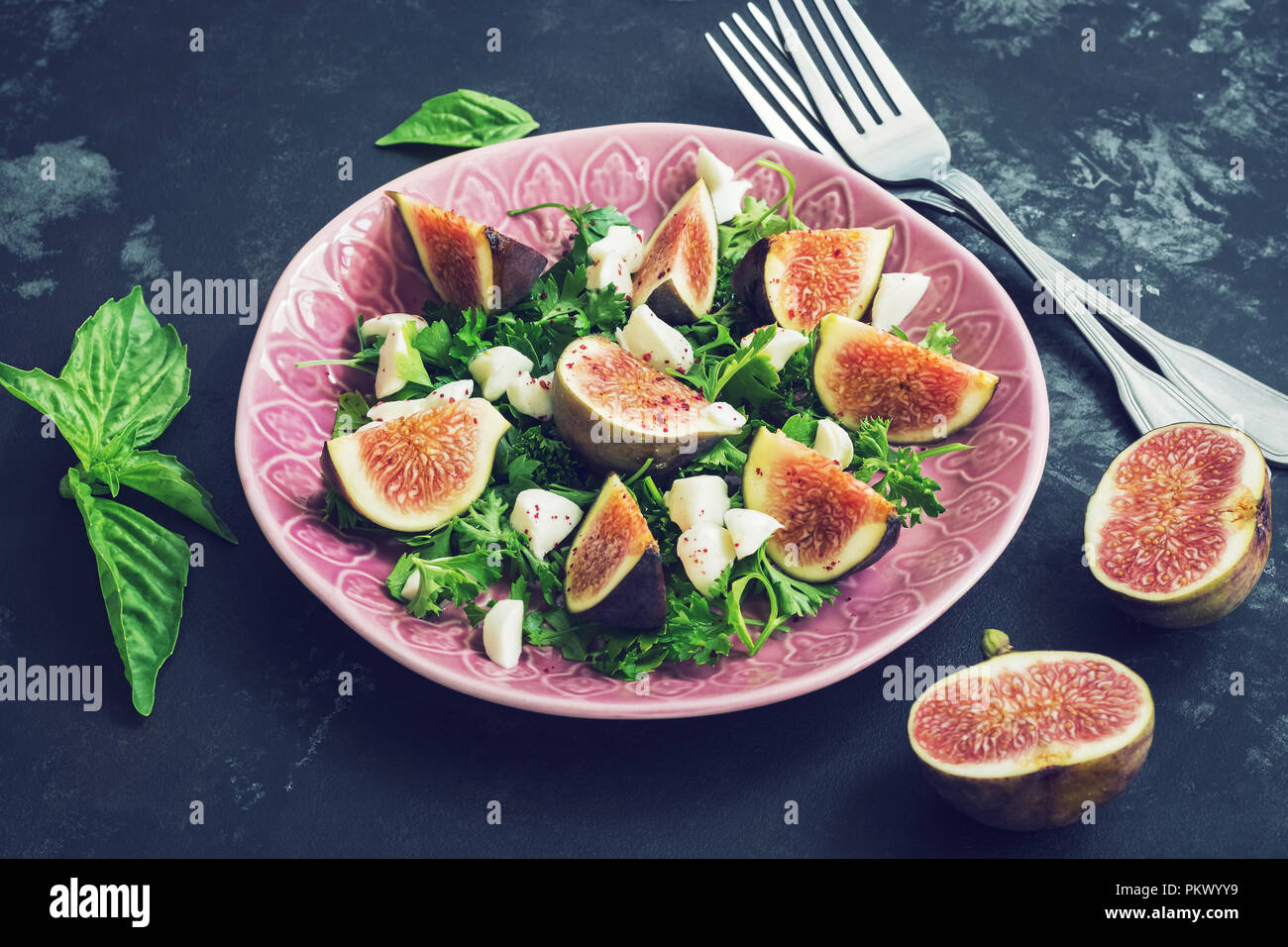 Delicious figs, green leaves, goat cheese, black background Toned photo Stock Photo