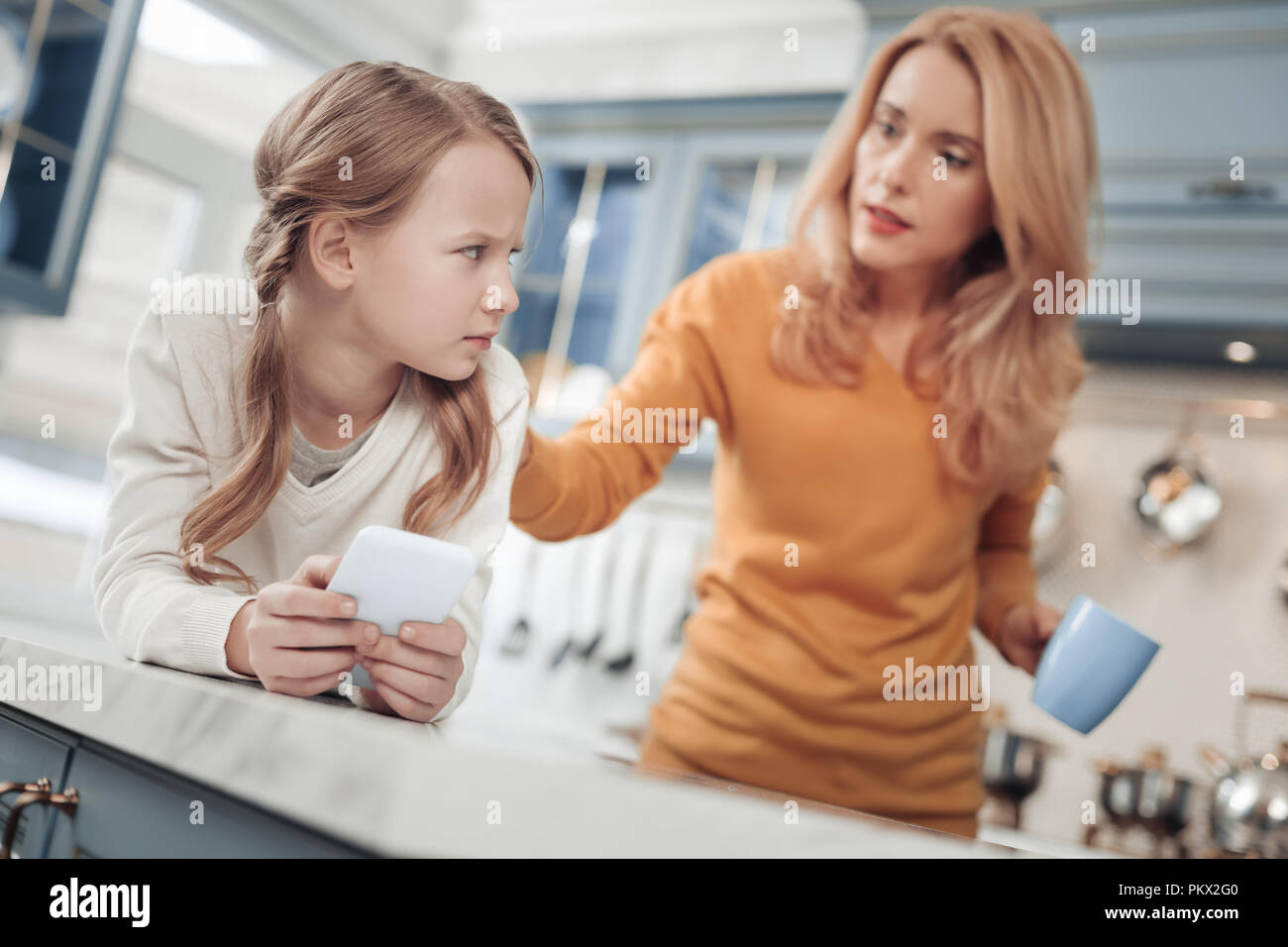 Angry little female pupil looking at her mother - Stock Image