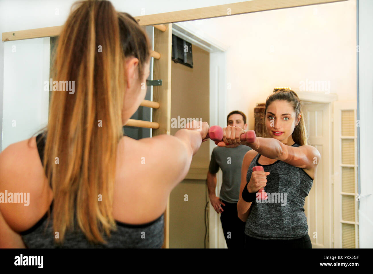 Sports woman exercise with lifting weights at fitness center. Good looking young girl doing boxing kick directly in gym. Sport, fitness, healthy. - Stock Image