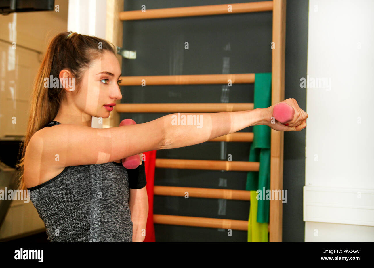 Sports woman exercise with lifting weights at fitness center. Good looking young girl doing boxing kick directly in gym. Sport, fitness, healthy - Stock Image