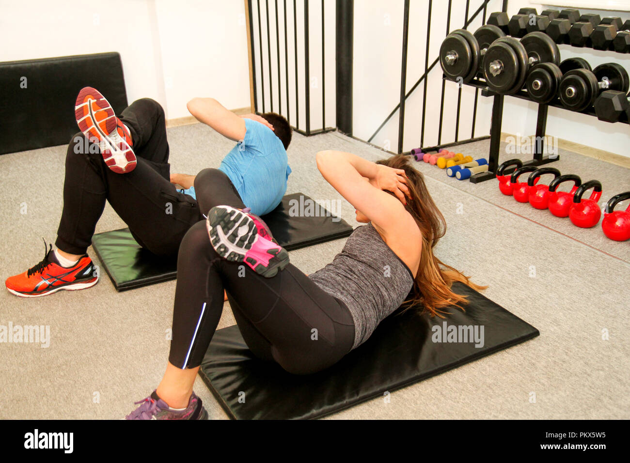 Sporty people doing stomach abs exercises at gym club. Happy fit young pretty couple in training working out stomach on mat in fitness studio. - Stock Image
