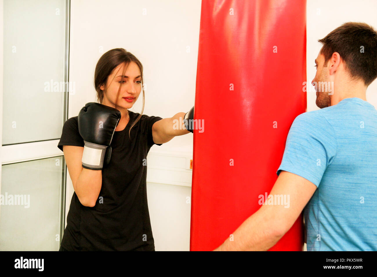 The female boxer training at gym. Young sporty woman punching her male partner with red boxing gloves at gym club. Attractive sports girl. - Stock Image