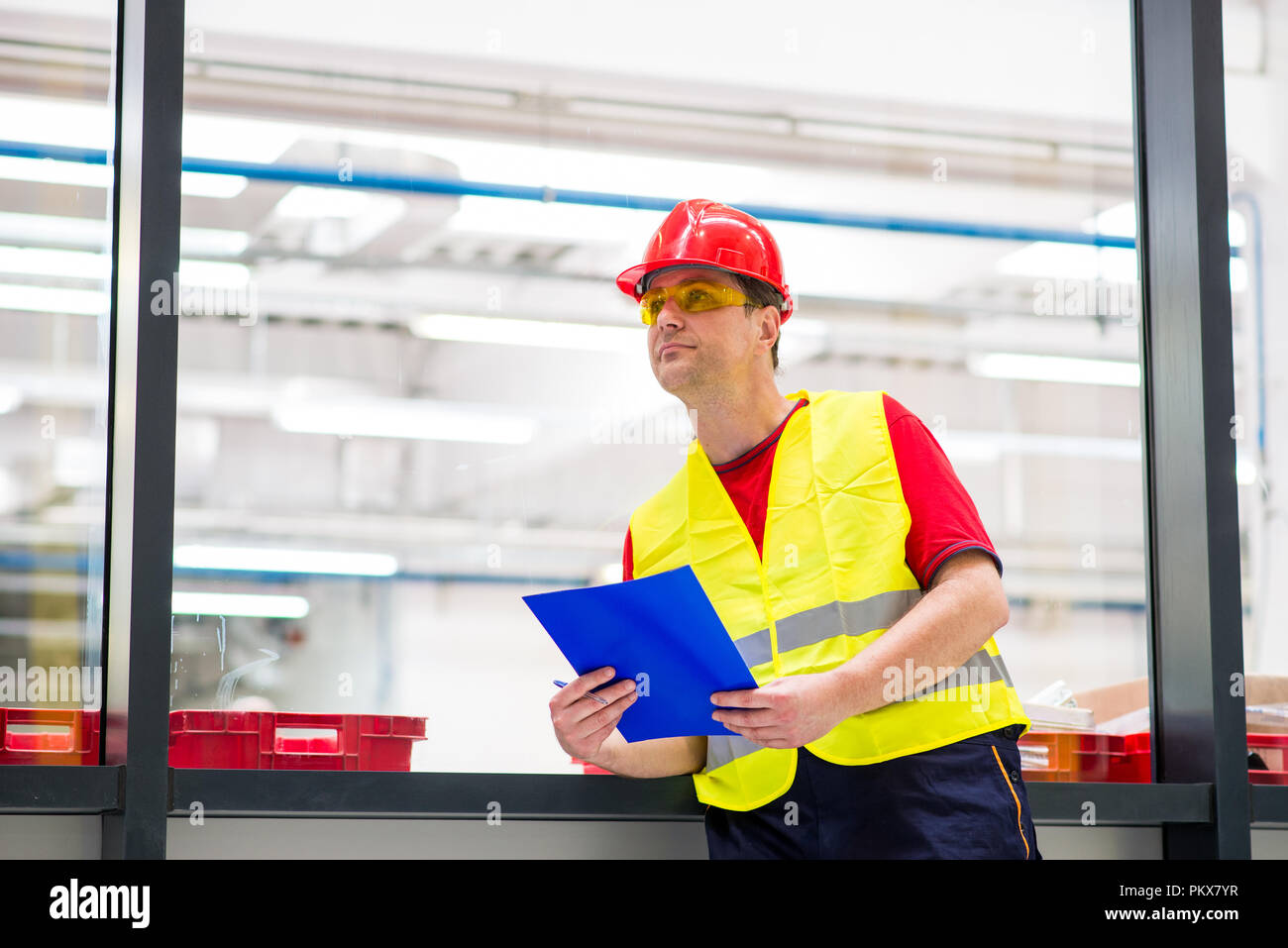 Factory supervisor in yellow reflective west with red helmet. Factory engineer holding blue folder with documents - Stock Image