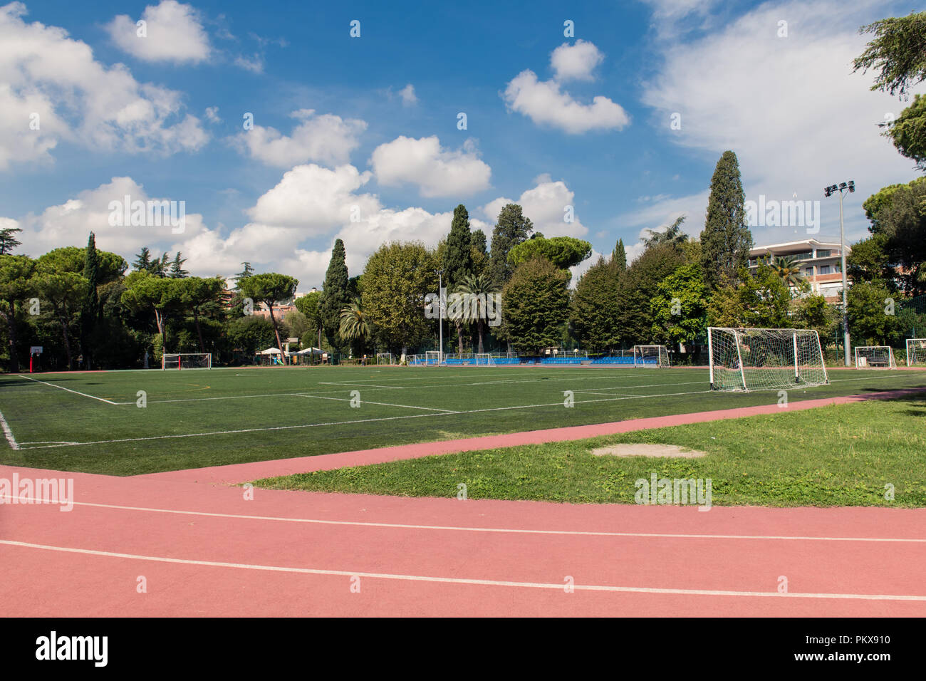 Wide shot of green football field in park with athletic track and trees around, no people landscape view - Stock Image