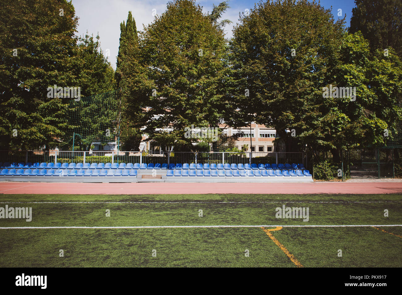 Blue stand seats line wide shot in park with green sports field - Stock Image