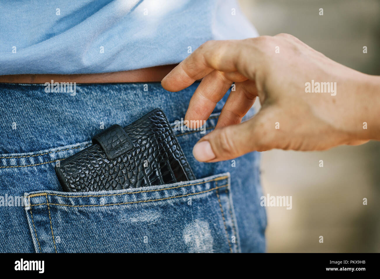 Theft of a purse from a jeans pocket in the daytime on the street, close-up - Stock Image