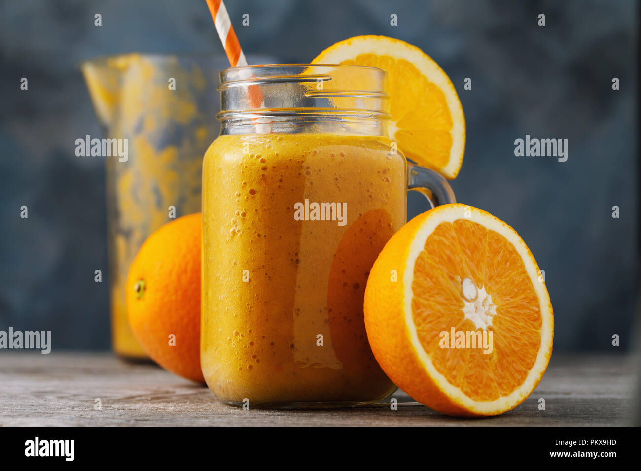 Vitamin drink: smoothies from fresh oranges in a glass jar on a wooden table, close-up - Stock Image