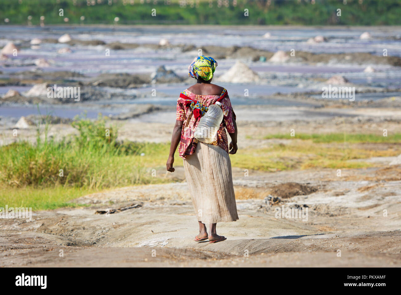 Woman Carrying Water in Plastic Bottle, Uganda, East Africa - Stock Image