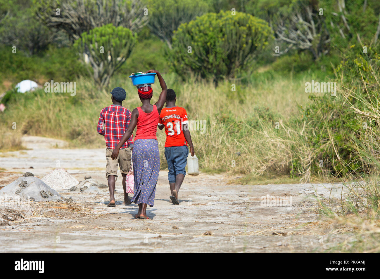 African Woman Walking Carrying Basin on Head and Two Young Men Walking, Africa Woman Carries Load on top of her Head, Uganda - Stock Image