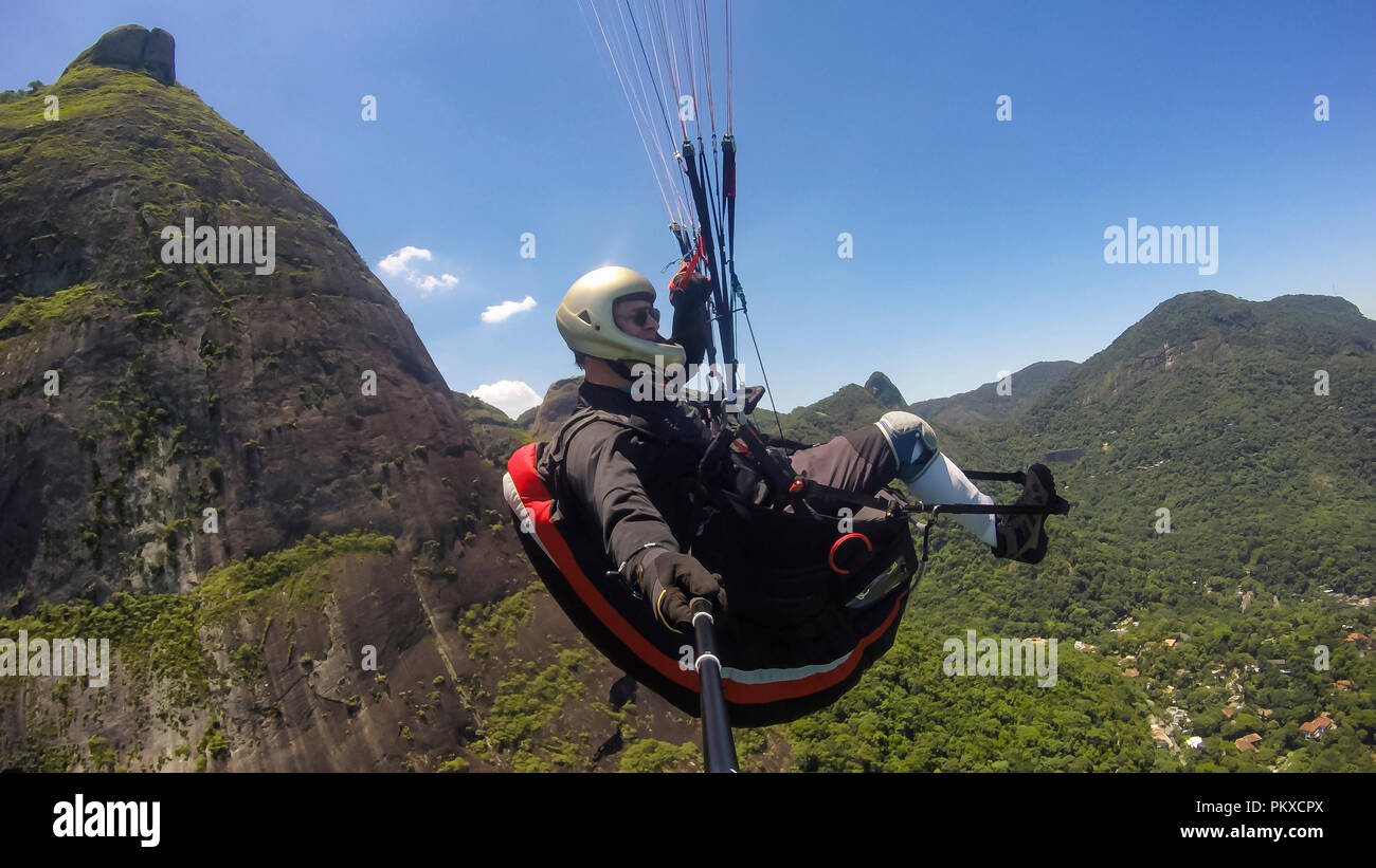 Paraglider pilot, physical handicapped, flying in their own paragliding. Stock Photo