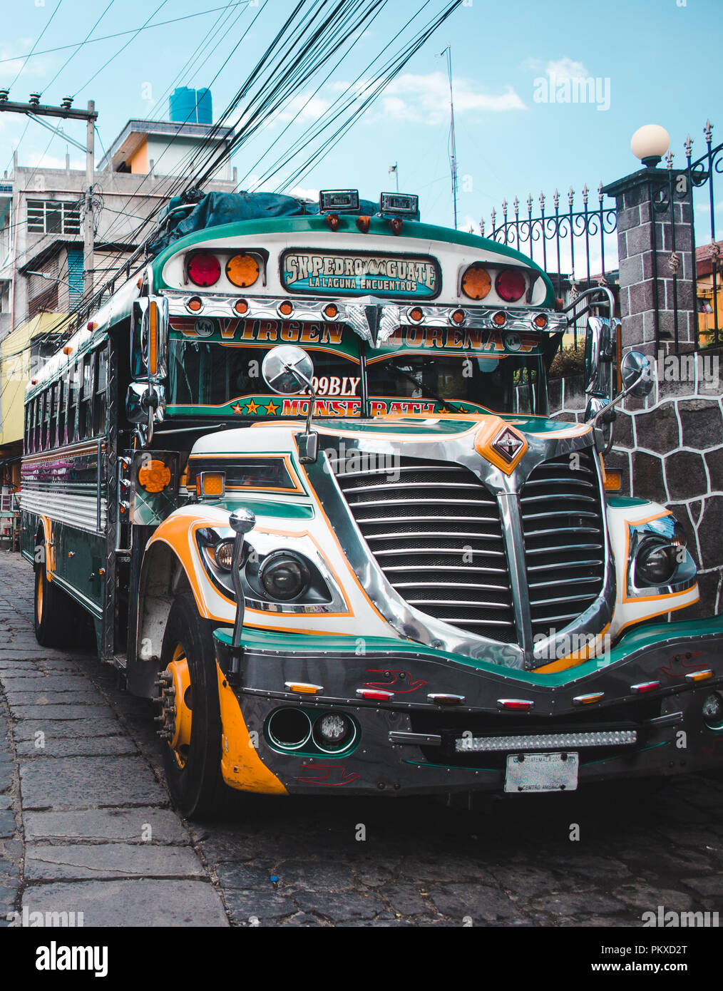 A colorful public bus - also known as 'chicken bus' - parked in San Pedro Guatemala. An example of a repurposed and repainted American school bus - Stock Image