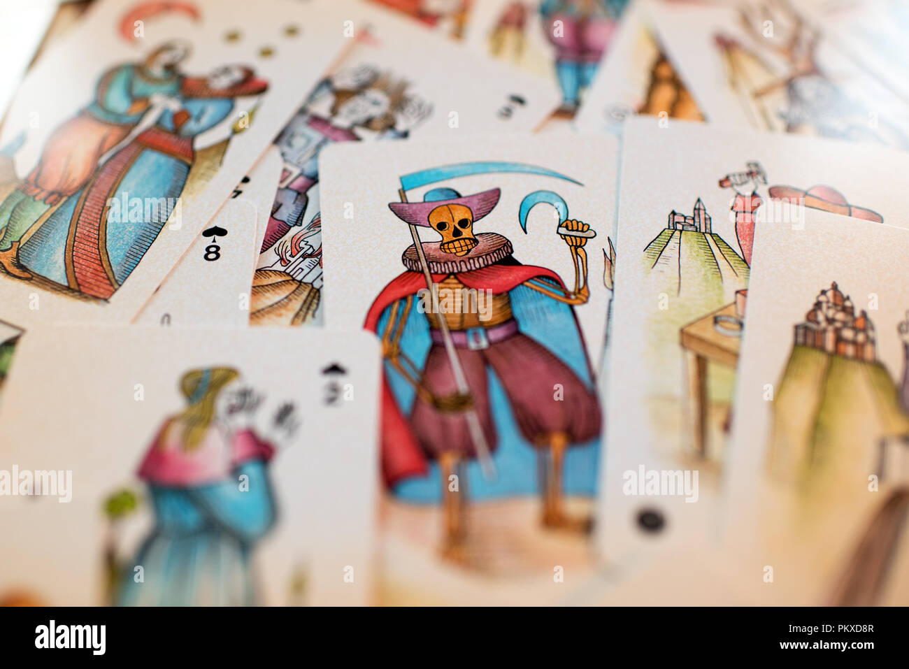 Background of scattered tarot cards with focus to the pictorial card of the Grim reaper symbolic of Death in the centre in a full frame view - Stock Image