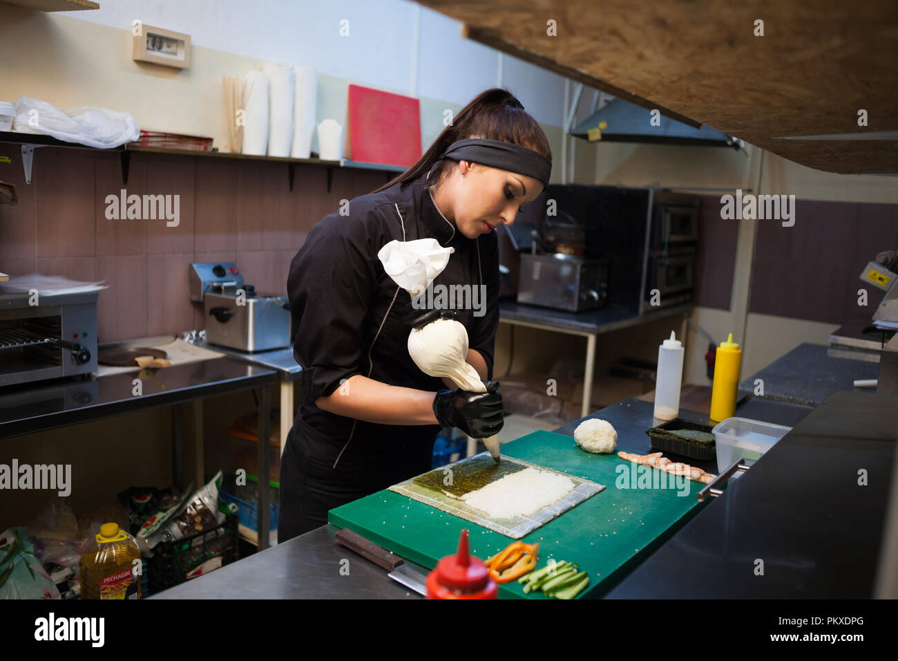 woman Cook prepares sushi on restaurant kitchen - Stock Image