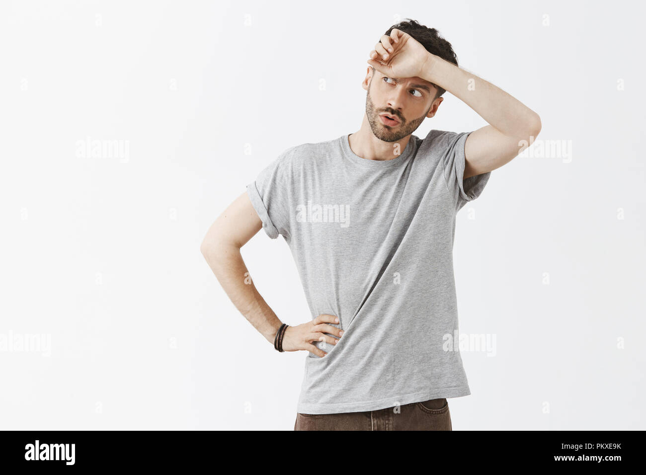 Phew so close. Portrait of relieved handsome dark-haired man with beard in grey t-shirt whiping sweat from forehead breathing out with folded lips and gazing left, solving hard problem - Stock Image