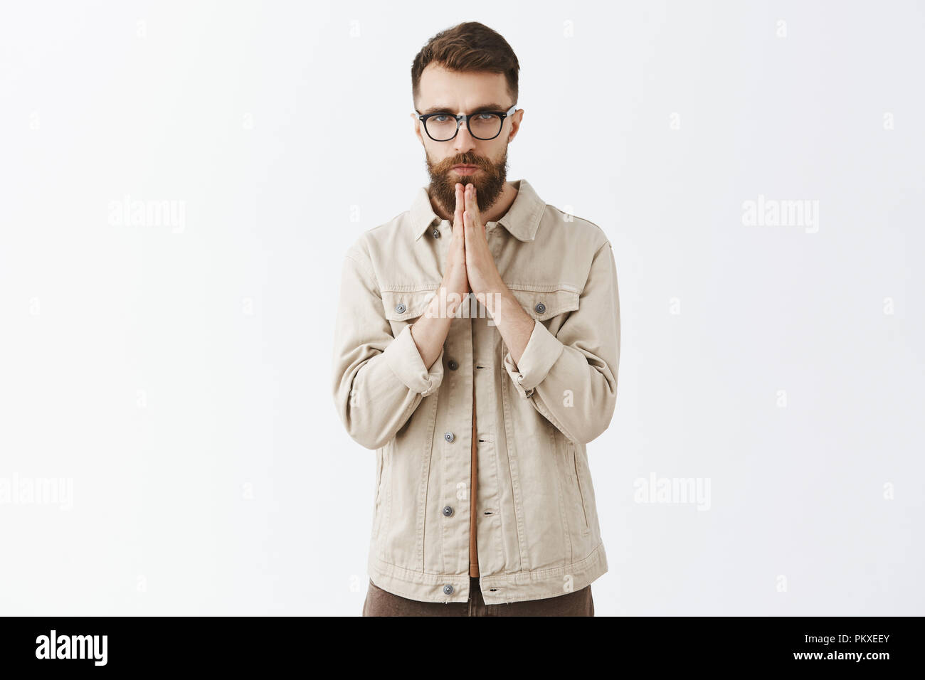 Indoor shot of gloomy unhappy and sad adult man with long beard in beige outdoor jacket holding hands in pray standing with serious unemotional expression begging for money or praying - Stock Image