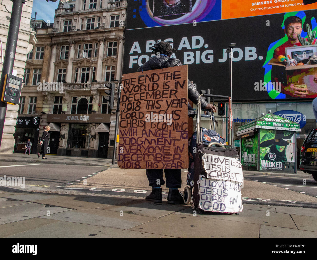 A man wearing a sandwich board predicting the end of the world walks through Piccadilly Circus in central London Stock Photo