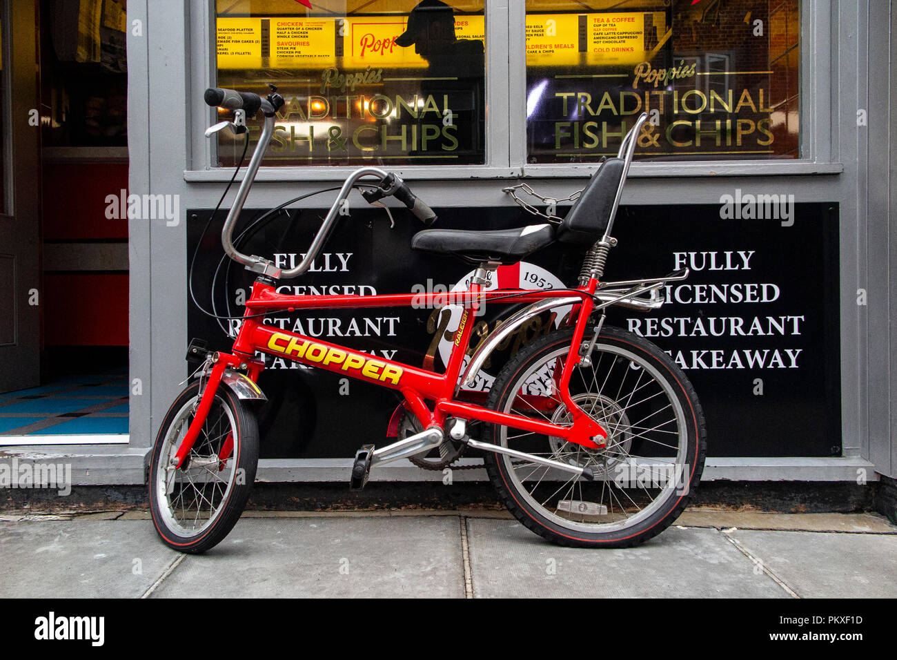 An immaculate Raleigh Chopper parked outside a fish and chip shop in London's Soho - Stock Image