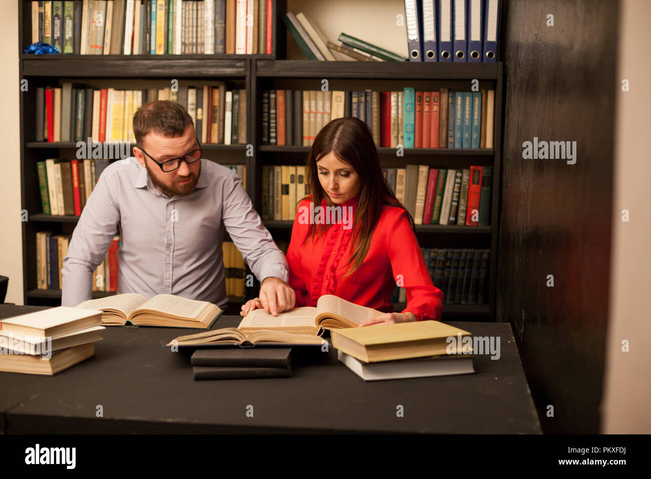 a man and a woman read books in the library are preparing for the exam 1 - Stock Image